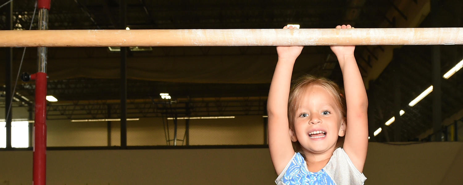 Girl hanging from gymnastics bar