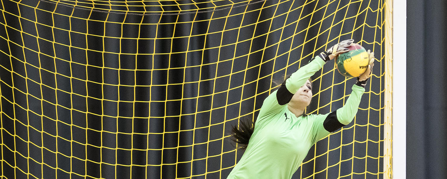 Woman goalie making soccer save