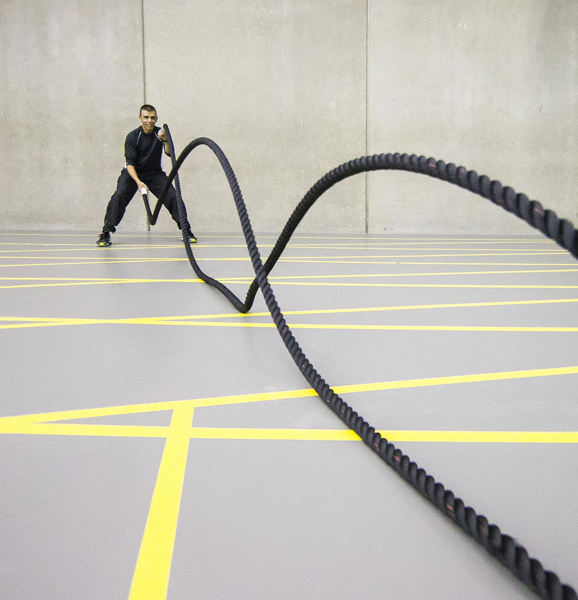 Man working out with battle ropes in Fitness Centre