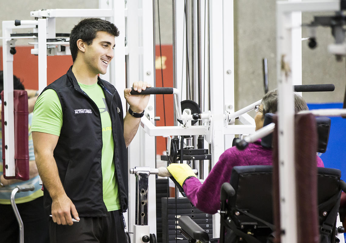 Trainer helps UCalgary Rehabilitation Fitness Program participant with stretches