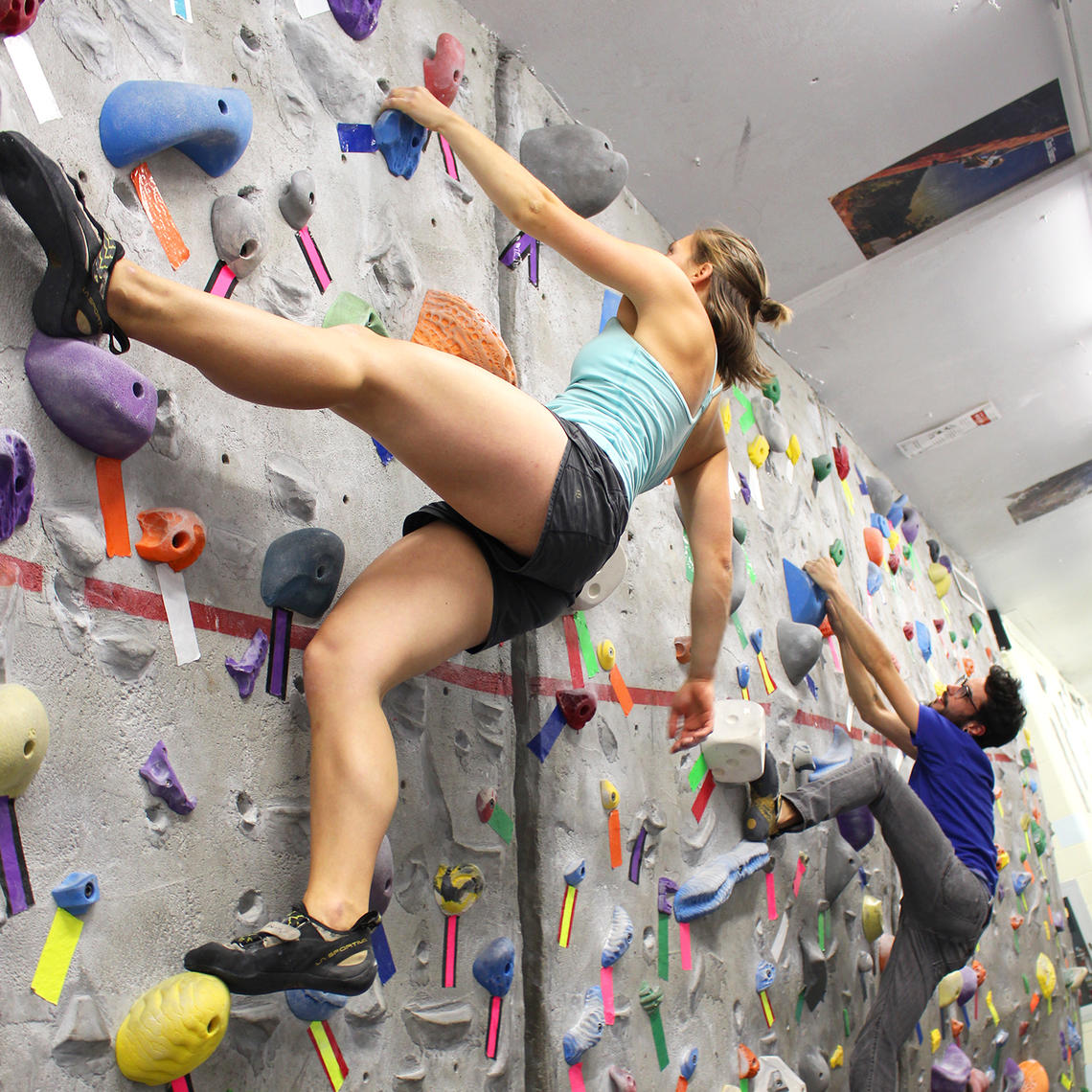 Woman and man climbing bouldering wall