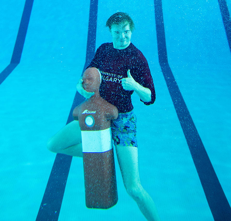 UCalgary lifeguard gives thumbs up under water