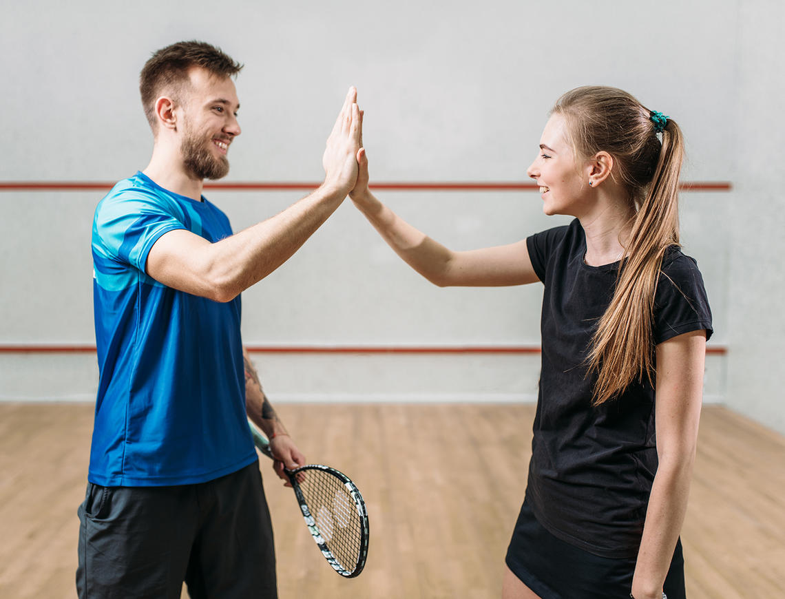 Squash players high five because they love following the rules