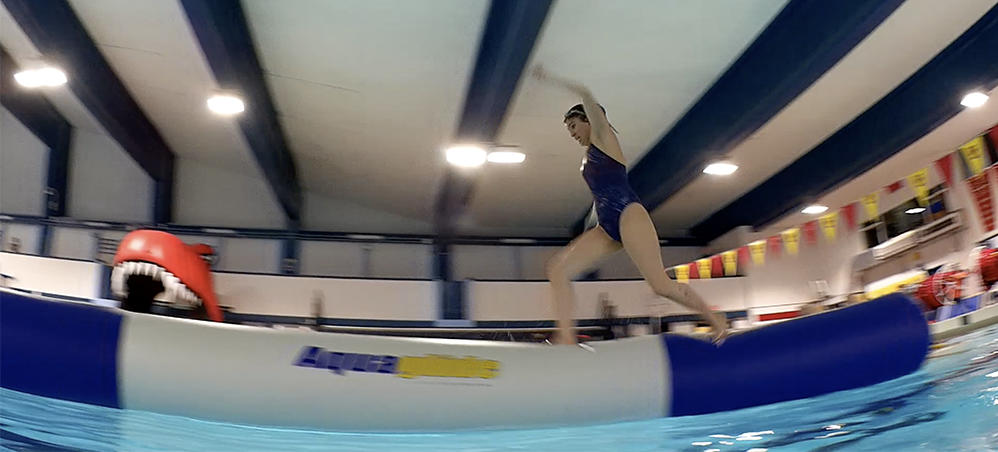 Swimmer runs across inflatable obstacle at University of Calgary pool