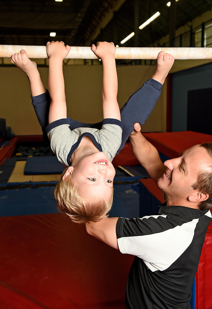 Coach helping kid on gymnastics bar - Cochrane