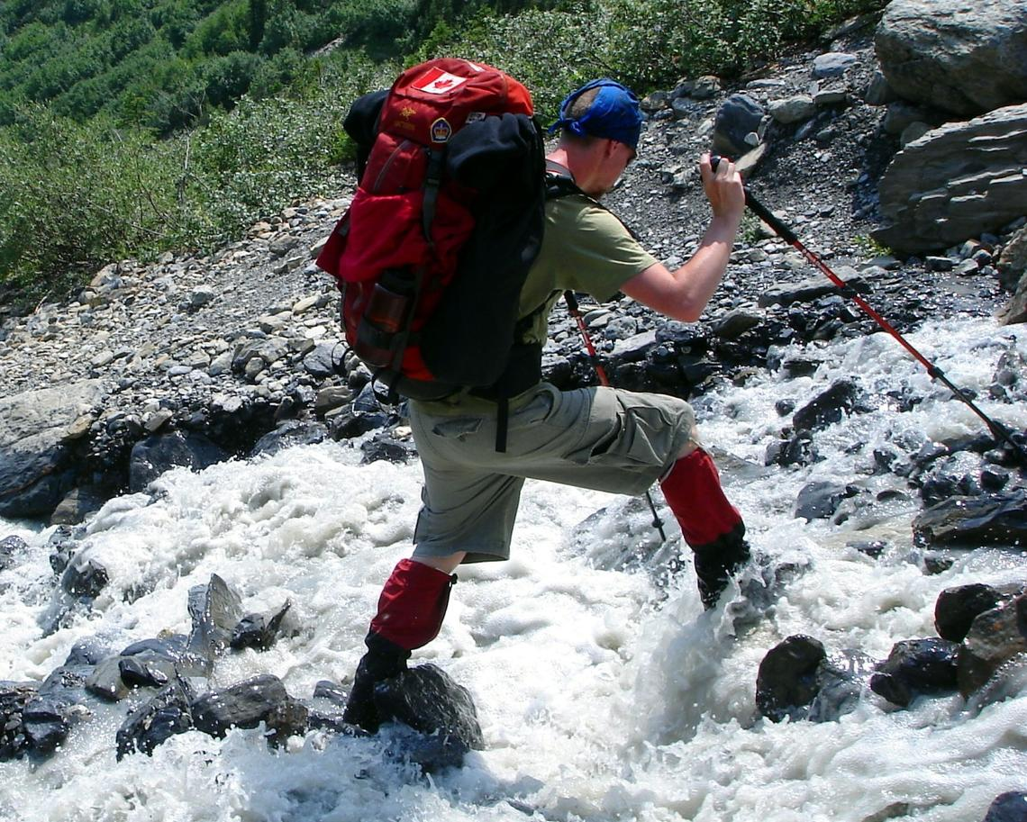 Man hiking across rocks in water using poles