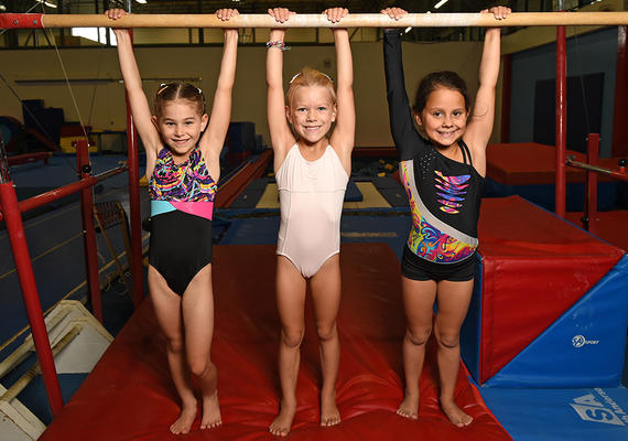 Girls hanging from gymnastics bar