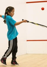 Girl learning how to play racquet sports at UCalgary